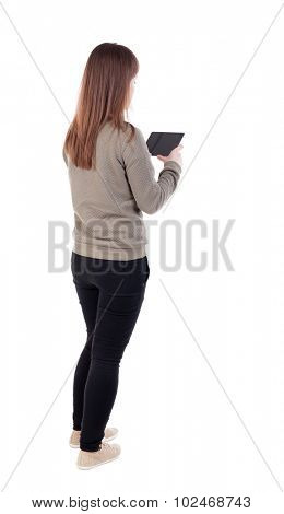 Back view of woman photographing. girl photographer in jeans. Rear view people collection.  backside view person. Isolated over white background. Sitting girl enthusiastically photographing something