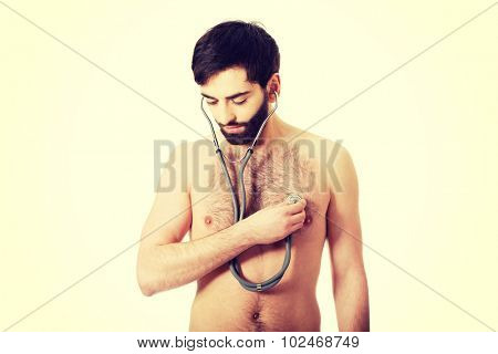 Young man measuring his heartbeat with stethoscope.