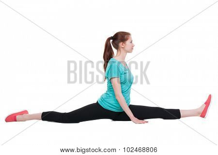 side view of the girl in sportswear sitting on  splits. Rear view people collection.  backside view of person.  Isolated over white background. Girl sitting on the splits and look to the left.