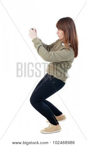 Back view woman photographing.   girl photographer in jeans. Rear view people collection.  backside view person.  Isolated over white background. Sitting girl enthusiastically photographing something.