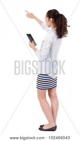 back view of pointing young beautiful  girl with tablet computer. girl  watching. Rear view people collection.  backside view of person.  Isolated over white background.