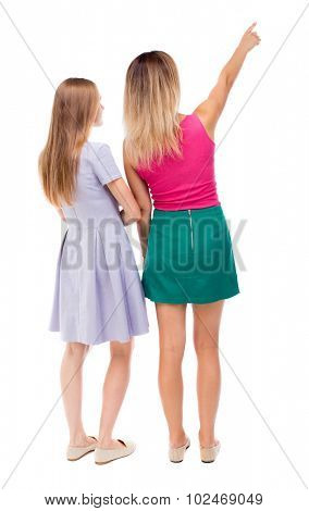 Back view of two pointing young girl. Rear view people collection.  backside view of person. beautiful woman friends  showing gesture. Rear view. Isolated over white background.