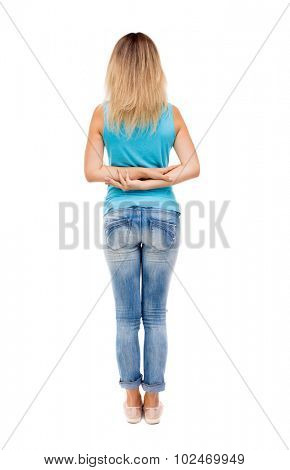 back view of standing young beautiful  woman.  girl  watching. Rear view people collection.  Isolated over white background. The girl in jeans and a blue shirt stands with his arms crossed on his back