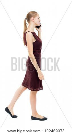 a side view woman walking with a mobile phone. beautiful curly girl in motion.    Rear view people collection. Isolated over white background. girl in a burgundy dress talking on phone and walks away