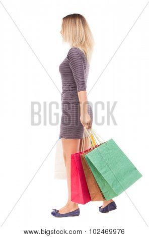 back view going woman with shopping bags. beautiful brunette girl in motion.  backside view person.  Rear view people collection. Isolated over white background. girl in purple dress is left with bags