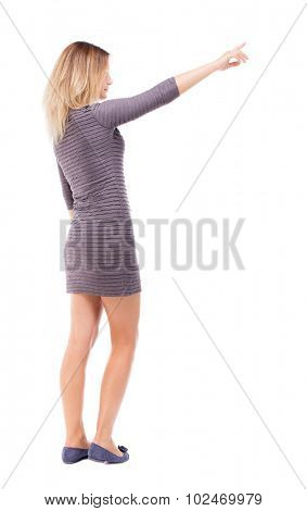 Back view of  pointing woman. beautiful girl. Rear view people collection.  backside view of person.  Isolated over white background. A girl in a purple dress stands sideways and points to the right.
