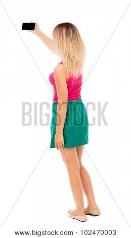 back view of standing young beautiful  woman  in vest and using a mobile phone. girl  watching. Isolated over white background. Blond girl in a green skirt pictures of something on your smartphone.