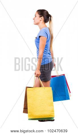 back view of going  woman  with shopping bags . beautiful brunette girl in motion.  backside view of person. Isolated over white background. Girl in a gray skirt and blue blouse carries purchases left