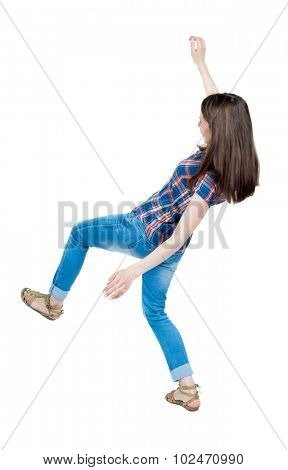 Back view woman Balances waving his arms.   Standing young girl in jeans. .  Isolated over white background. A young girl in a checkered blue with red stripes and slipped trying not to fall.