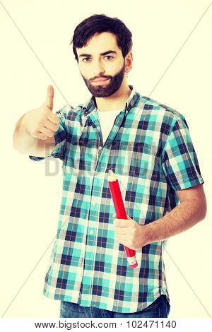 Young man with oversized red pencil and thumbs up.