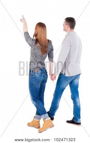 Back view of walking young couple (man and woman) pointing. Rear view people collection. backside view of person. Isolated over white background/ The guy and the girl go and look at the sky.