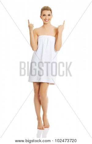 Beautiful happy spa woman wrapped in towel pointing up.