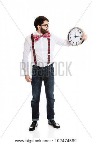 Funny man wearing suspenders holding big clock.