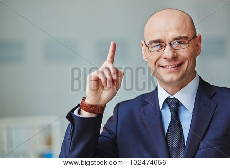 Elegant businessman looking at camera and pointing upwards