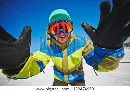 Snowboarder in sportswear and goggles standing in front of camera