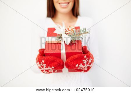 Girl in mittens showing giftbox with Christmas present