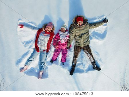 Happy family of three having fun in snowdrift