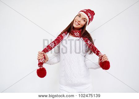 Happy girl in cap, sweater and scarf looking at camera