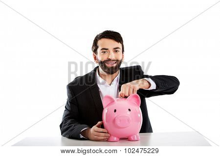Young successful businessman putting a coin to piggybank.