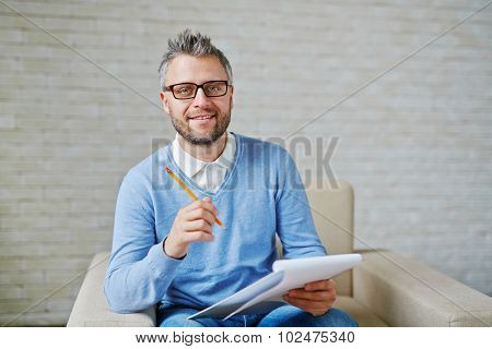 Male psychiatrist with pencil and clipboard looking at camera