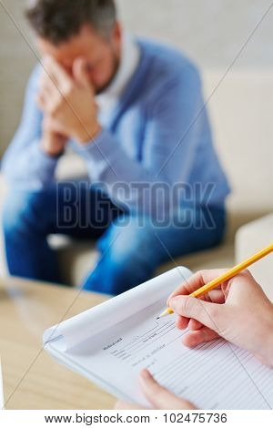 Hands of psychiatrist filling in medical document in front of stressed patient