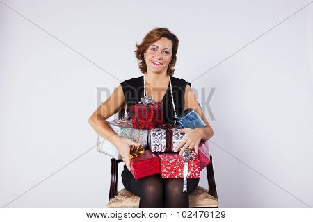 Woman sited on a chair holding gifts