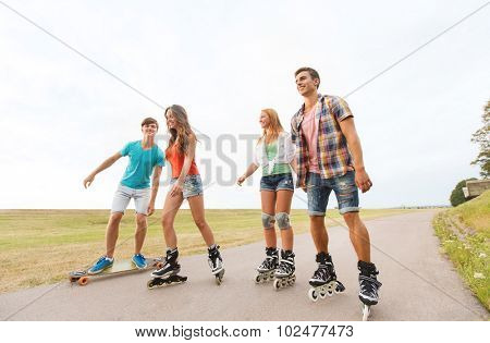 summer holidays, leisure, sport, love and people concept - group of happy teenage friends with rollerblades and longboards