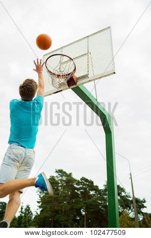 sport, game and basketball concept - young man throwing ball into basket outdoors