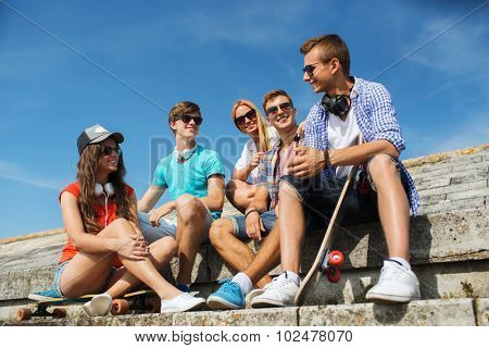 people, leisure and sport concept - group of happy teenage friends with longboard and headphones talking on city street