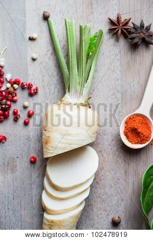 Spices, parsley root and herbs on wooden background.