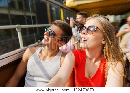 travel, tourism, summer vacation, sightseeing and people concept - happy teenage couple in sunglasses traveling by tour bus