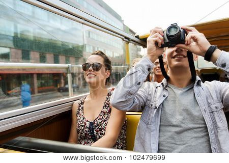 travel, tourism, summer vacation, sightseeing and people concept - smiling teenage couple with camera traveling by tour bus and photographing