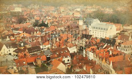 Roofs of Bruges,  Belgium. Top view on the historic center.  Photo in retro style.  Added paper texture