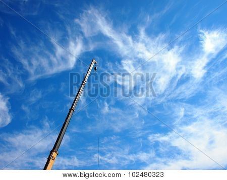 The Boom Of The Crane On A Diagonal Against A Blue Sky