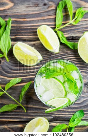 Mojito cocktail in glass on a rustic wooden background