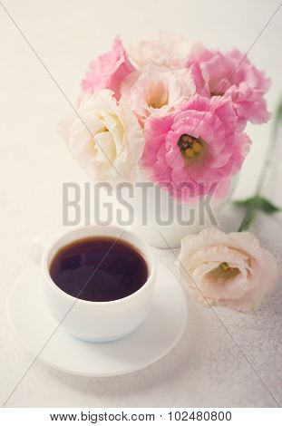 Still life with cup of coffee and flowers (Eustoma). Shallow depth of field. Toned image