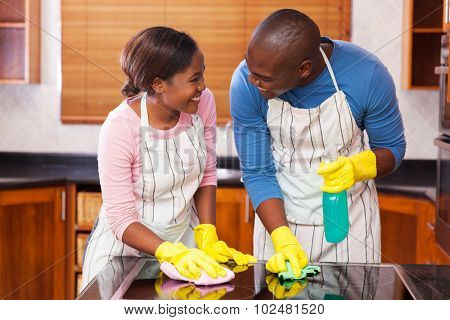 lovely young black couple cleaning together in their kitchen