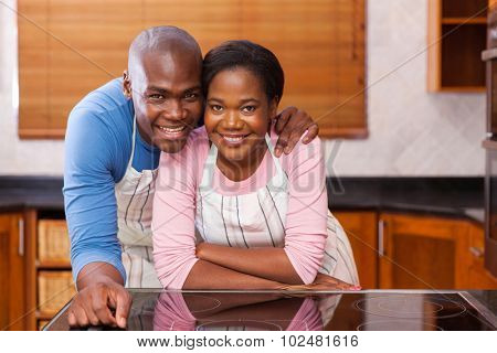 portrait of happy african couple leaning against the kitchen counter