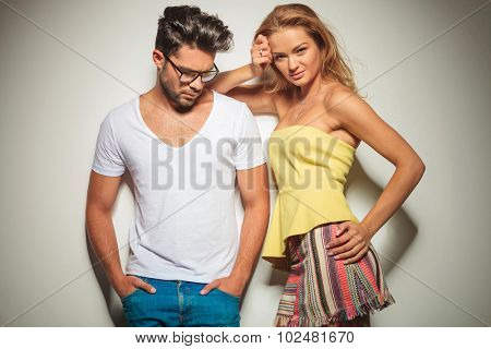 man with glasses holds hands in pockets and looks down while woman poses leaning to his shoulder