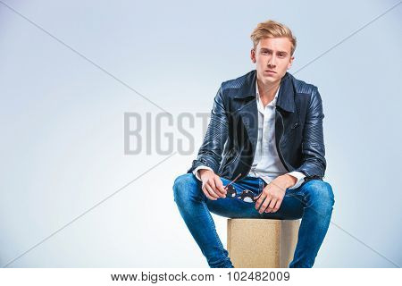 young skinny blonde boy taking off his glasses and posing while sitting on a box