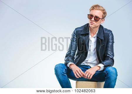 young skinny man wearing sun glasses and leather jacket while sitting on a box