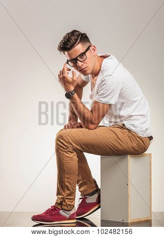 young man sitting on a chair thinking and looking at the camera