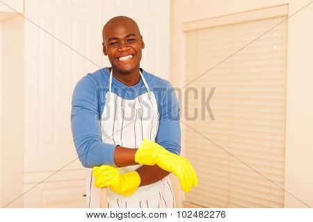 portrait of cheerful african man cleaning his bedroom
