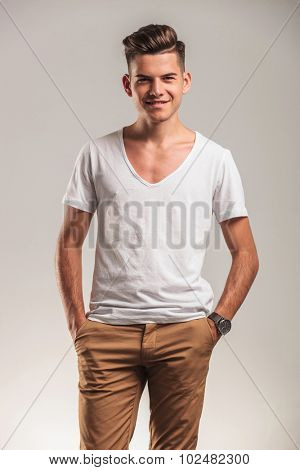 picture of a handsome young man smiling at the camera while holding hands in pockets