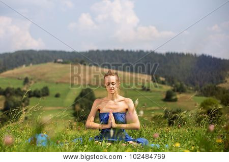 Young girl meditating and praying in the park
