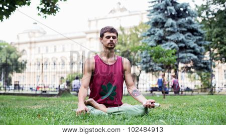 a handsome young man sitting in meditation in a park is holding a phone in his hand and listening t
