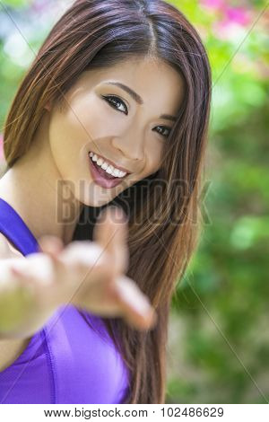 Outdoor portrait of a beautiful young Chinese Asian young woman or girl with perfect teeth, reaching to camera.