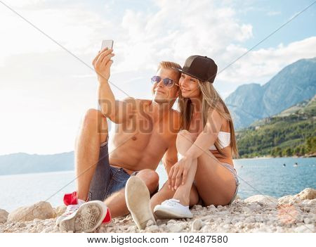 Couple Sitting On A Beach And Taking A Selfie