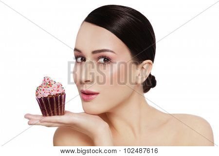 Young beautiful girl with excited expression and tasty cupcake in her hand over white background, copy space