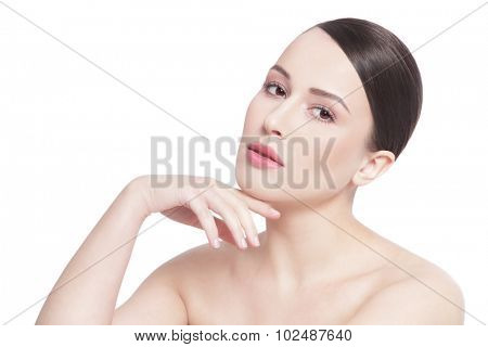 High key portrait of young beautiful healthy happy woman touching her face and looking upwards over white background, copy space